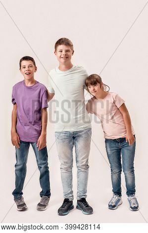 Full Length Shot Of Three Cheerful Teenaged Disabled Children With Down Syndrome And Cerebral Palsy
