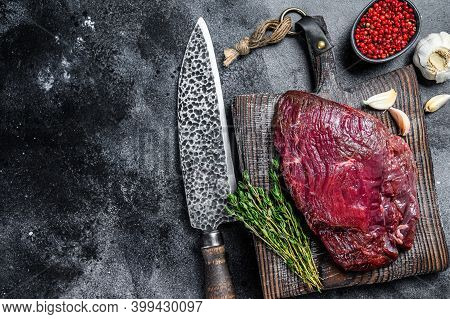 Venison Raw Deer Meat On A Cuuting Board With Herbs. Black Background. Top View. Copy Space