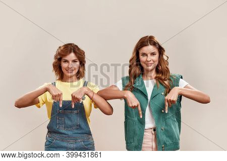 Portrait Of Two Attractive Young Girls, Twin Sisters In Casual Wear Smiling At Camera, Pointing Down