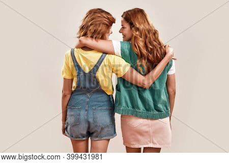 Back View Of Two Young Girls, Twin Sisters In Casual Wear Embracing, Looking At Each Other, Posing T