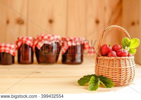 Strawberry jam in a jar on a wooden background with fresh strawberries in a basket.