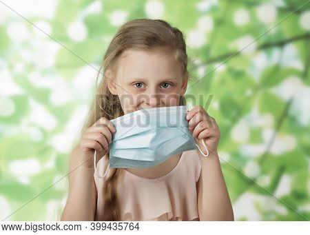 Cute Beautiful Blonde Girl Puts On A Face Mask On A Green Background