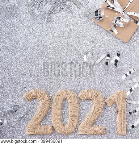 Top View. Inscription 2021 Made Of Twine On A Silver Background Decorated With Sparkling Ribbon And
