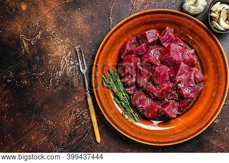 Raw Diced Deer Steak For A Venison Goulash. Dark Background. Top View. Copy Space
