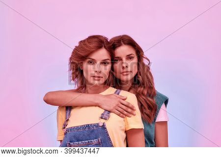 Portrait Of Two Attractive Young Girls, Twin Sisters Looking At Camera, Posing Together Isolated Ove