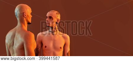Portrait Of Young Half Naked Twin Brothers With Tattoos And Piercings Looking At Each Other, Posing