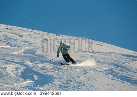 LES ORRES, FRANCE - CIRCA2015: Young skier coming down fast in fresh powder snow off-piste.