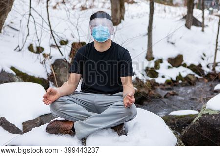 Full Frontal Shot Of Man In A T-shirt Sitting In The Yoga Lotus Flower Position On A Big Rock In The