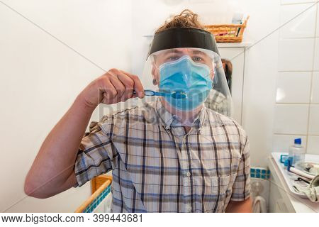Funny And Ironical Shot Of A Young Man In His Bathroom Trying To Wash His Teeth With And Over A Covi