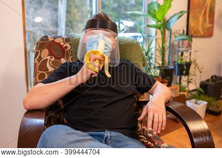 Medium Close Shot Of A Young Man Relaxing In An Armchair Indoor And Eating A Banana, Wearing Protect