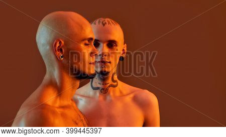 Front And Side View Of Young Half Naked Twin Brothers With Tattoos And Piercings Posing Together, St