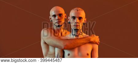 Portrait Of Young Half Naked Twin Brothers With Tattoos And Piercings Looking At Camera, Posing Toge