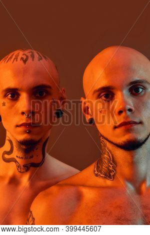Close Up Portrait Of Young Half Naked Twin Brothers With Tattoos And Piercings Looking At Camera, Po