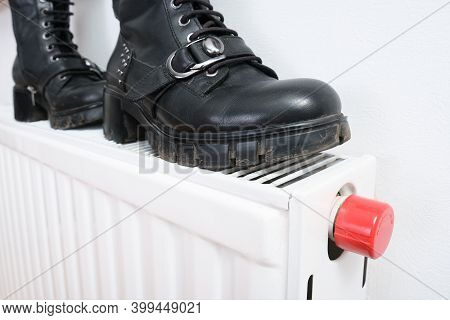 Wrong Drying Of Footwear, A Pair Of Dirty Leather Winter Shoes On A Hot Central Heating Radiator