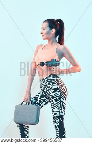 Athletic Young Female In Sportswear Posing With Handheld Massage Gun For Post-workout Recovery In Ne
