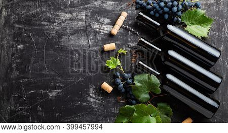 Wine Bottles, Grapes, Grape Bunches With Leaves And Vines Corkscrew Wine Corks On Dark Rustic Concre