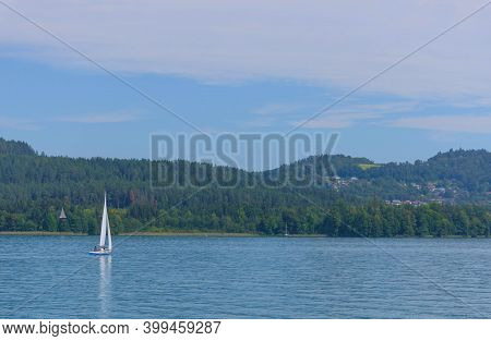 Boating And Sailing On The Clear Waters Of Alpine Lake Worthersee, Famous Tourist Attraction For Man