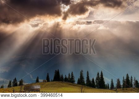 The sun's rays break through the clouds and illuminate the valley. Location place of Carpathian mountains, Europe. Vibrant photo wallpaper. Image of a bright epic sky. Discover the beauty of earth.