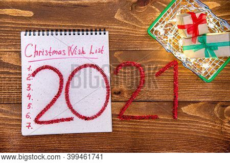 Christmas Composition Basket With Gifts, Garland, Wish List And Numbers 2021 New Year On A Wooden Ba