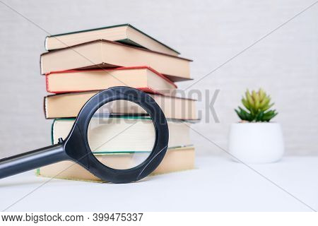 A Stack Of Books And Magnifying Lens, Loupe Lying On A White Table, Reading And Education Concept.
