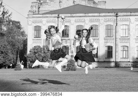 Driven And Energetic. Energetic Children In Midair Outdoors. School Girls In Energetic Jump. Back To