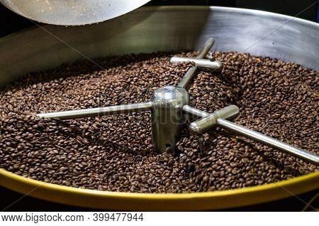 Freshly Roasted Coffee Beans From A Large Modern Coffee Roaster Are Stirred In The Cooling Cylinder