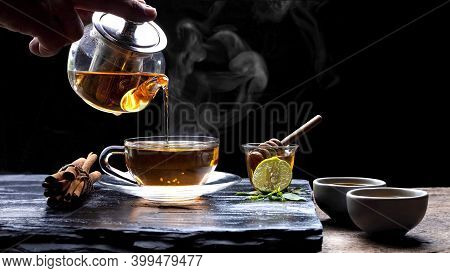 Pouring Hot Aromatic Herbal Tea From Teapot Into Glass Teacup Set With Steam And Various Herbs On Bl