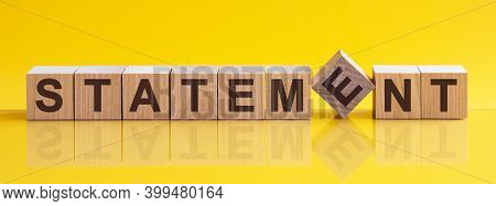 Statement Word Is Made Of Wooden Building Blocks Lying On The Yellow Table, Concept