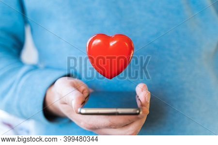Big Flying Red Heart. Mobile Phone, Smartphone In Hand Of Man. Valentine's Day Holiday Concept.onlin