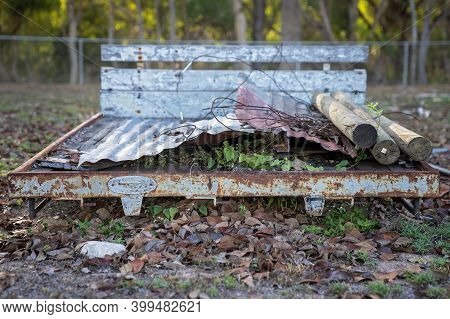 An Old Truck Tray Back Discarded Amongst Leaves And Piled With Sheets Of Iron And Logs In A Rural Ba