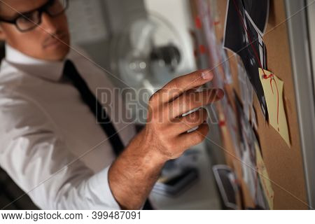 Detective Looking At Evidence Board In Office, Focus On Hand
