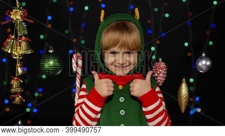 Teen Kid Girl In Christmas Elf Santa Claus Helper Costume Showing Thumbs Up Gesture, Agree Sign Isol