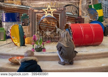 Children Look At Christmas Creche With Joseph Mary And Small Jesus In A Crib