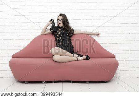 Sexy Woman Resting On Sofa. Beautiful Girl Sit On Sofa. Sexy Brunette Businesswoman. Desire And Temp