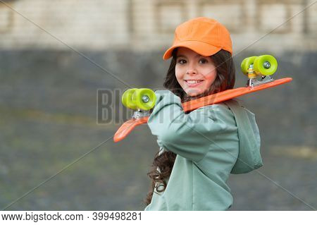 Life Is A Lot With Skateboarding. Happy Girl Hold Penny Board Outdoors. Street Skateboarding. Sport