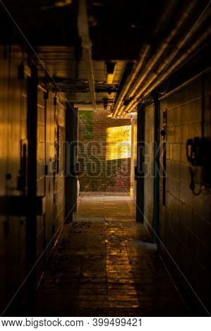 A Dark Hallway Inside An Abandoned Dormatory With Orange Light At The End Of It