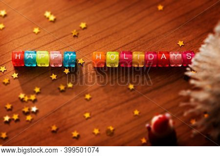 Happy Holidays. Alphabet cubes with sprinkled gold stars. Shallow depth of field. Low key.