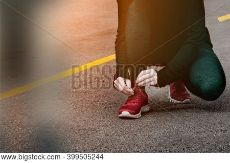 Young Woman Tying Shoelaces Before Jogging On Road In The Morning.