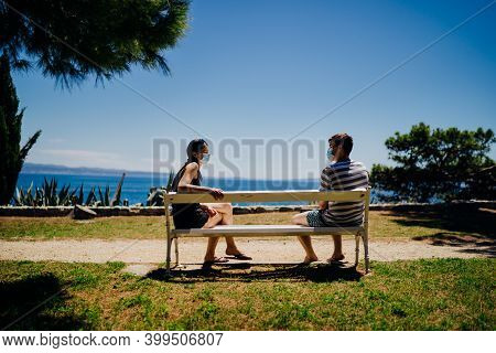 Young Couple Having An Outdoor Date On A Bench In A Park.social Distancing Dating.friends Talking, W