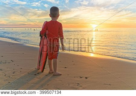 Little Boy Holding Body Board Whilst Standing At The Beach And Watching Sunset