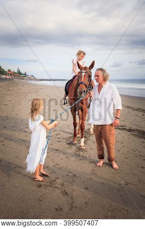 Little Girl On A Horse. Father And Daughter Leading Horse By Its Reins On The Beach. Horse Riding. F