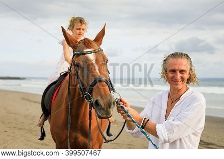 Little Pretty Girl On A Horse. Father Leading Horse By Its Reins On The Beach. Horse Riding. Family