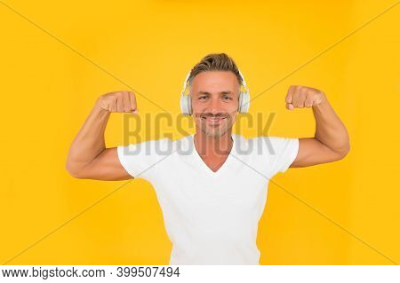 Happy Athletic Man Listen To Music In Headphones Flexing Strong Arms Yellow Background, Strength.