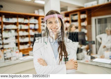 Friendly Pharmacist Working In A Pharmacy Amid Coronavirus Pandemic.pharmaceutical Health Care Profe