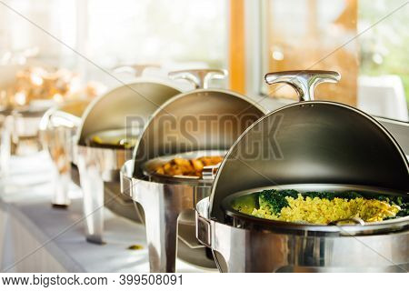 Elegant Chafing Dishes And Food Warmers With Various Meals Served For Catering Reception In Hotel Or