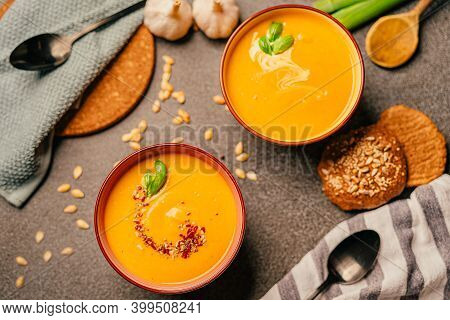 Vegetarian Autumn Roasted Pumpkin And Carrot Cream Soup With Seeds And Fresh Herbs In Colorful Bowls