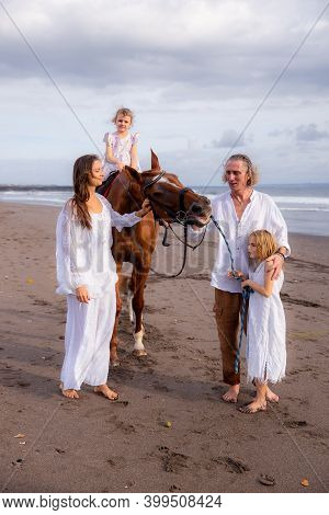 Horse Riding. Little Pretty Girl On A Horse. Father Leading Horse By Its Rein And Talking To Daughte
