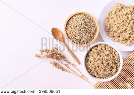 Cooked Brown Quinoa Seeds And Raw Quinoa Seeds In A Bowl On White Background, Top View, Healthy Vega