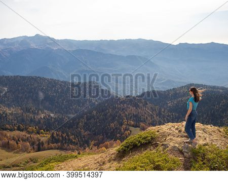 Hiking In The Mountains, Enjoy The Freedom At The Top. Young Female Tourist Alone On Top Of A Mounta