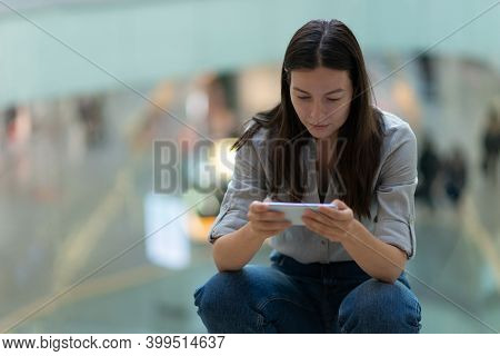 Young Woman Uses A Smartphone To Work And Communicate, Shallow Depth Of Field.